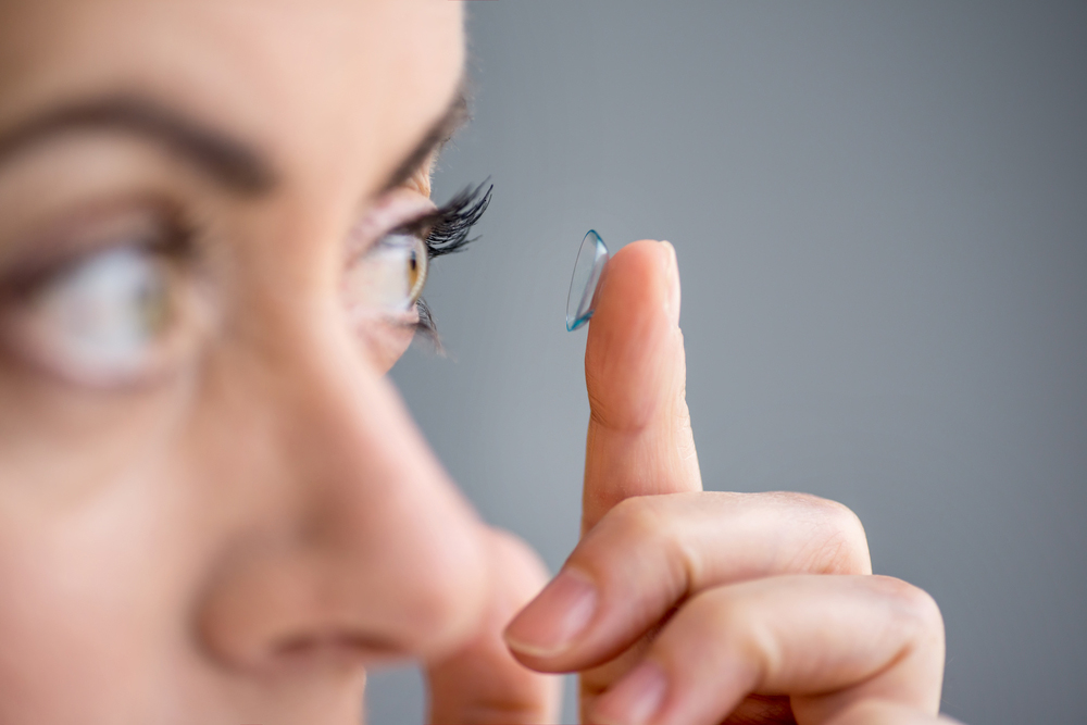 Woman putting on contact lenses